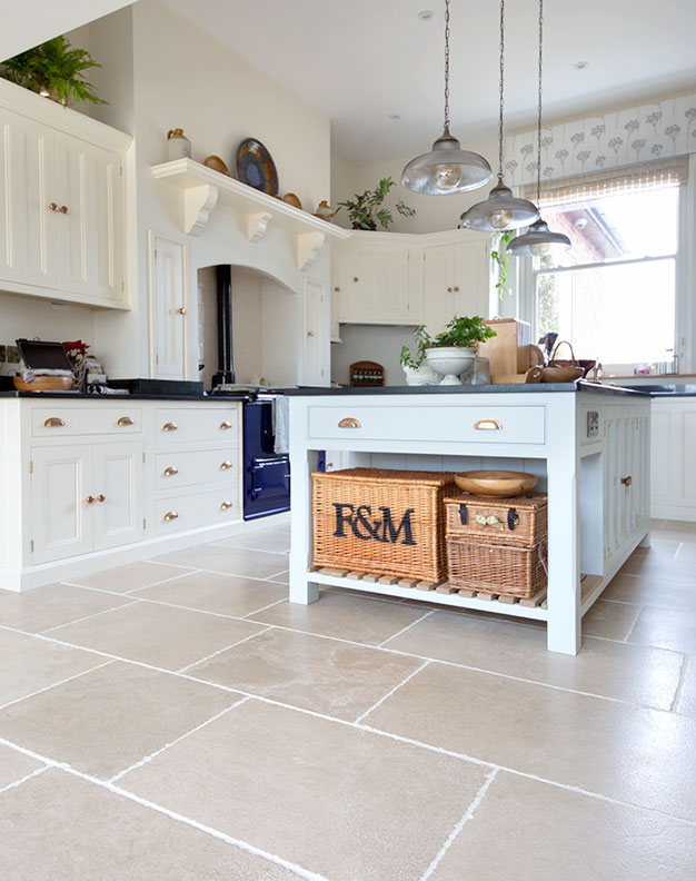 Close up photograph of pale blue island kitchen counter with rustic french limestone floor tiles