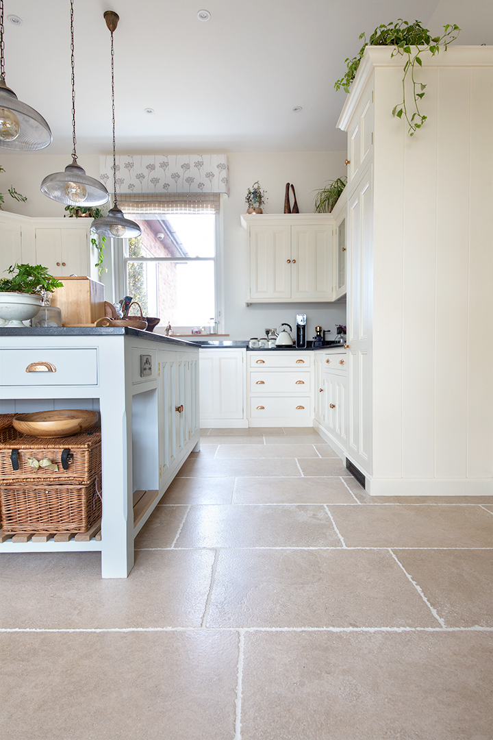 Detail photograph of modern rustic kitchen with white cupboards and french limestone floor tiles