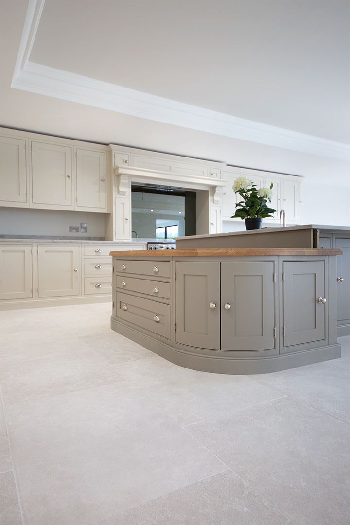 Photograph of modern kitchen with pale grey and white limestone floor tiles with a matte finish